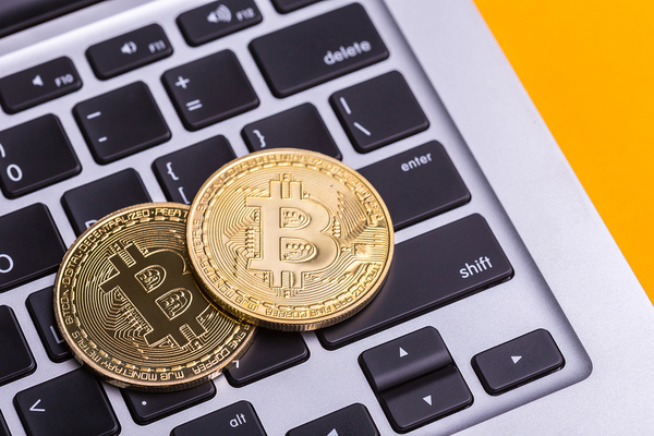 Two gold bitcoin coins on top of a laptop keyboard.