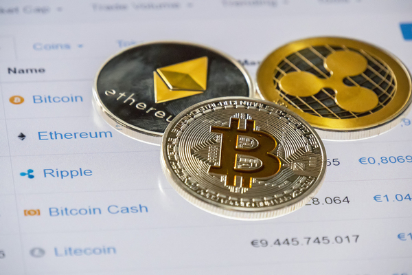 Gold and silver coins with bitcoin symbol, ripple symbol and ethereum symbol.