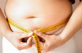 Teenager measuring her waist