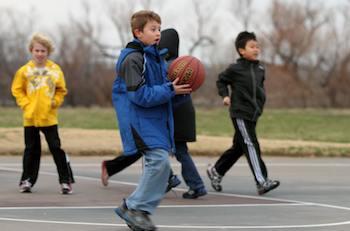 Boy celebración de baloncesto con otros niños en el fondo
