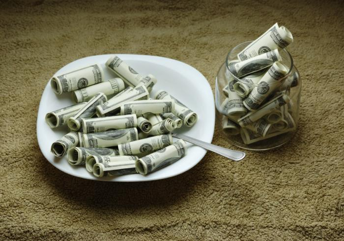 a dish and drinking glass both filled with dollar bills