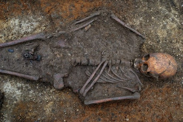 The skeleton and Christian cross as they were found in Trumpington Meadows, Cambs a site which has  been confirmed as one of the UK's earliest Christian burial sites.