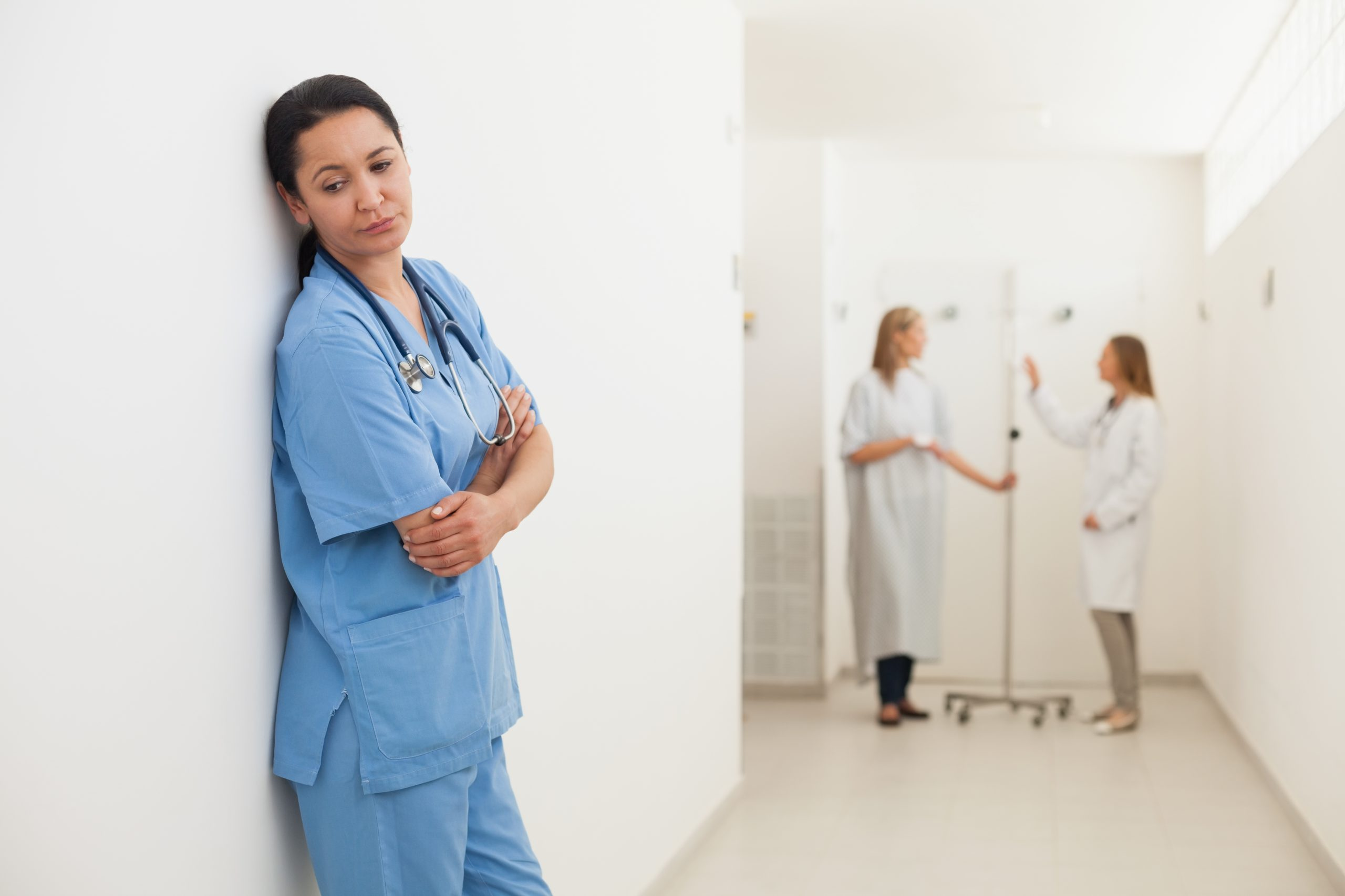 Nurse feeling sad with doctor talking to patient in hospital corridor. MEDIjobs
