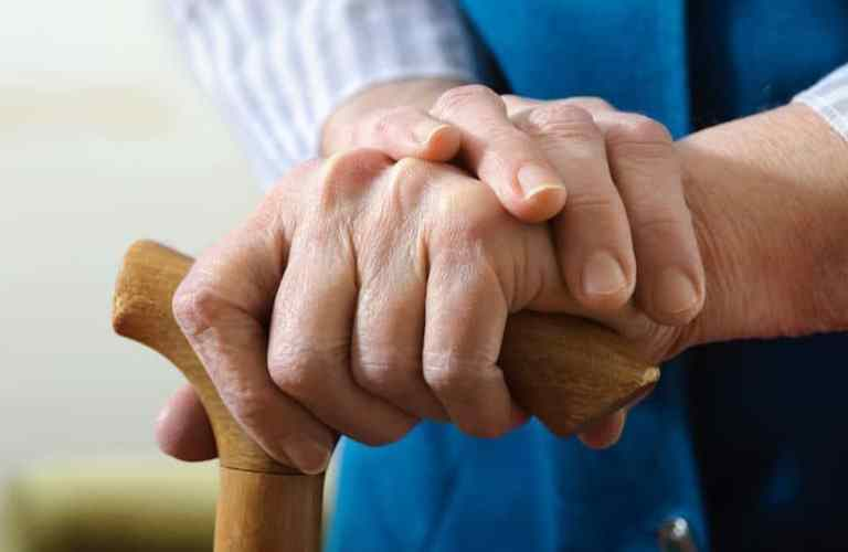 Gehstock mit Hand und Pflegerin