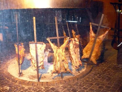 hier steckt das leckere Fleisch noch auf Spiesen um das Feuer