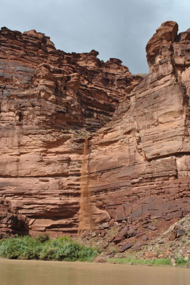 layered red sandstone with a small brown waterfall coming out of it from a short rainstorm on the green river