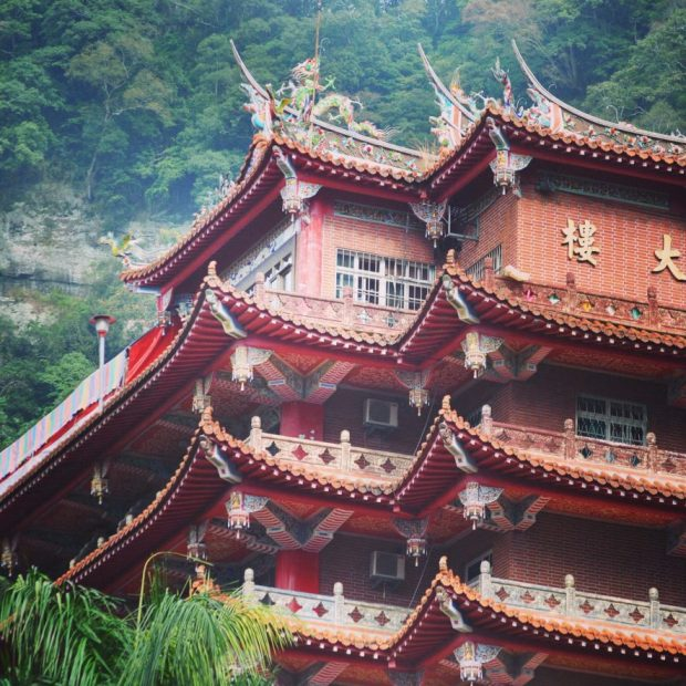 Chuan Hua Hall at Lion's Head Mountain nestled in lush green trees and built of bricks and ornate roofing
