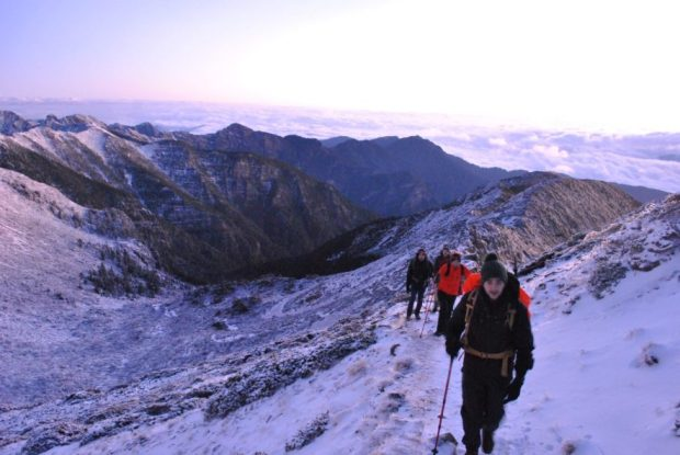 Single file hikers walking up to the summit of Snow Mountain at dawn in December with snow on the ground