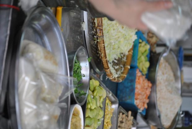 various fillings including shredded cabbage, lima beans, shrimp, bean curd in metal bowls at a street food stall in Taiwan