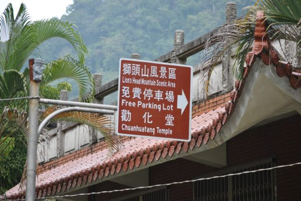 a brown sign in english and mandarin characters pointing towards Chuan Hua Hall, Lion's Head Mountain