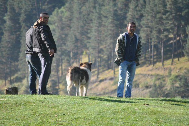men stand with a Caucasian sheep dog in Tusheti Georgia