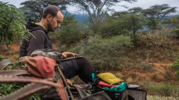 evan working on his laptop while wild camping in central Tanzania