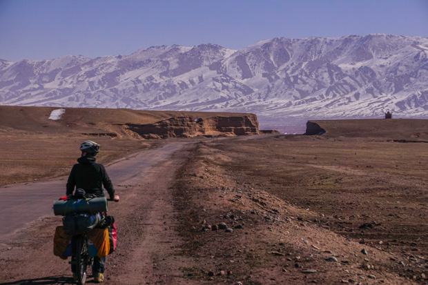 me on the road with my bicycle packed for winter, looking ahead at the snowy mountains of Kyrgyzstan