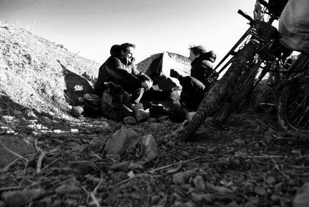 black and white photo of evan and i beside our tent and bicycles camping in a gully in Kyrgyzstan
