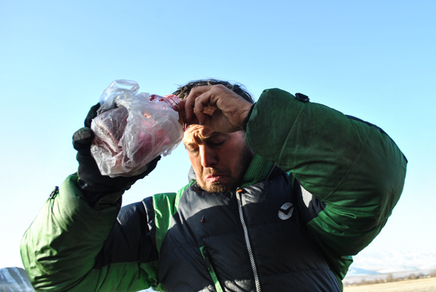 evan in a puffy winter jacket spills red jam from a glass jar while camping in Kyrgyzstan