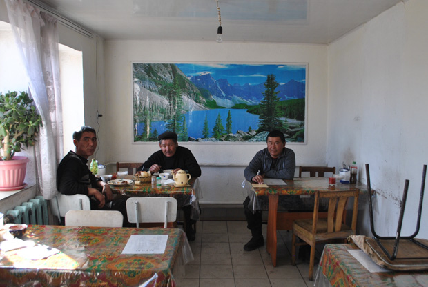 three male Kyrgyz truck drivers sit inside a small restaurant with a poster of mountains and a lake behind them