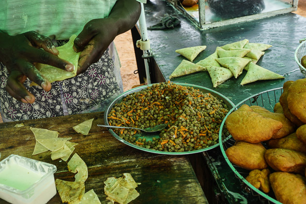a mans hands making samosas from a bowl of cowpeas and carrots near Kampala, Uganda
