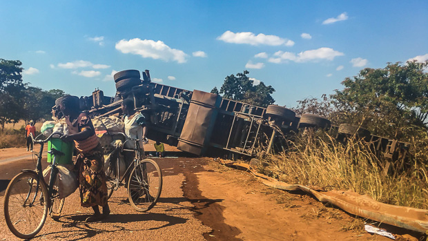 women pushing bicycles past an overturned semi truck on a dirt road in western Tanzani
