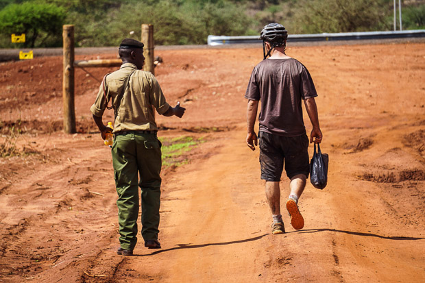 evan walking with a kenyan police officer outside Tsavo West National Park entrance