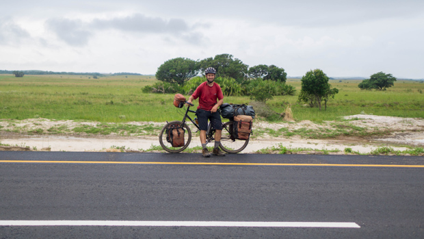 Evan posing with his bicycle on the new highway between Maputo and Ponta do Ouro, with a stand of palm trees behind him where we wild camped