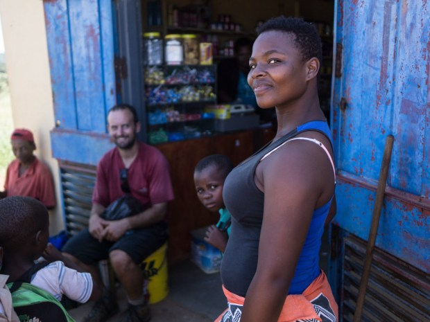 a young Swazi woman in a tank top smiles at me outside a rural shop with blue doors, Swaziland eSwatini