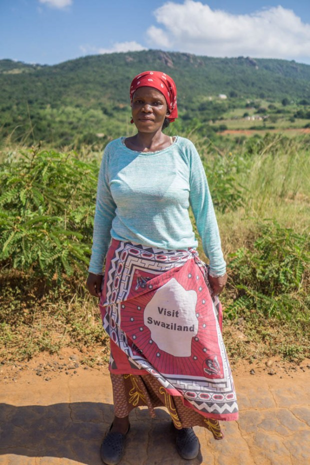 a woman wears a fabric wrap with graphics that say visit swaziland