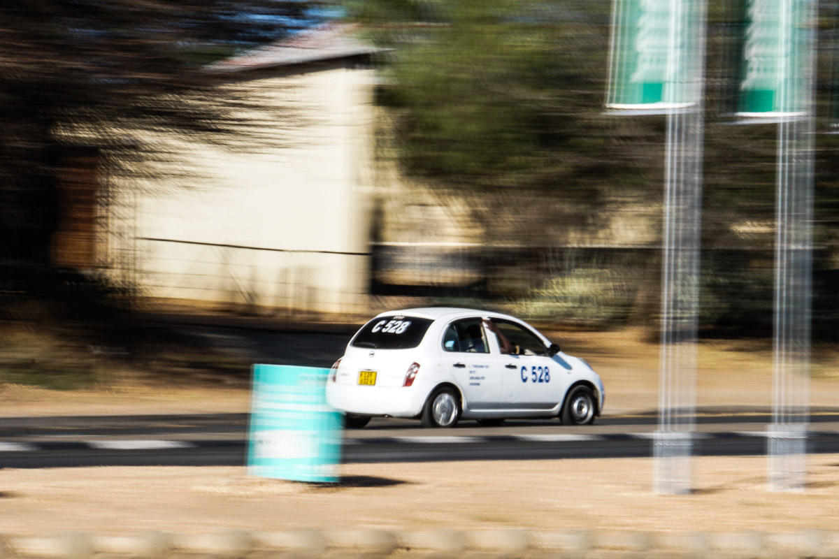 a white sedan taxi in Windhoek Namibia on the road