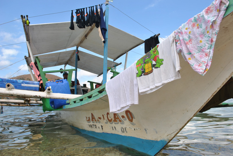 a bangka fishing boat ashore in Palawan, Philippines, with my laundry hanging on it