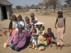 Vrouens en Kinders met huisies in agtergrond