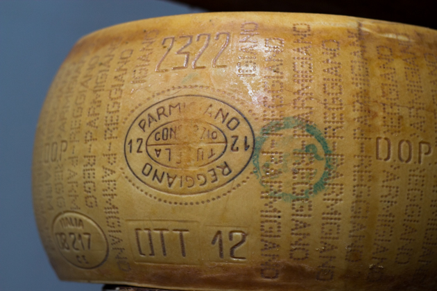 A WHEEL OF PARMIGIANO-REGGIANO CHEESE READY FOR THE MARKET WITH THE GREEN STAMP AND OVAL PARMIGIANO REGGIANO CONSORZIO TUTELA IMPRINT一轮准备上市的PARMIGIANO-REGGIANO奶酪,上面带有绿色的印章和椭圆形的PARMIGIANO-REGGIANO CONSORZIO TUTELA的印章