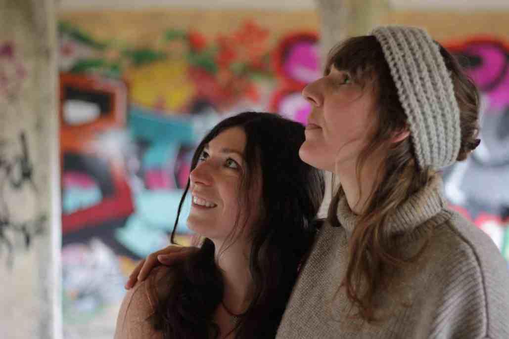 zwei Junge Frauen vor buntem Hintergrund