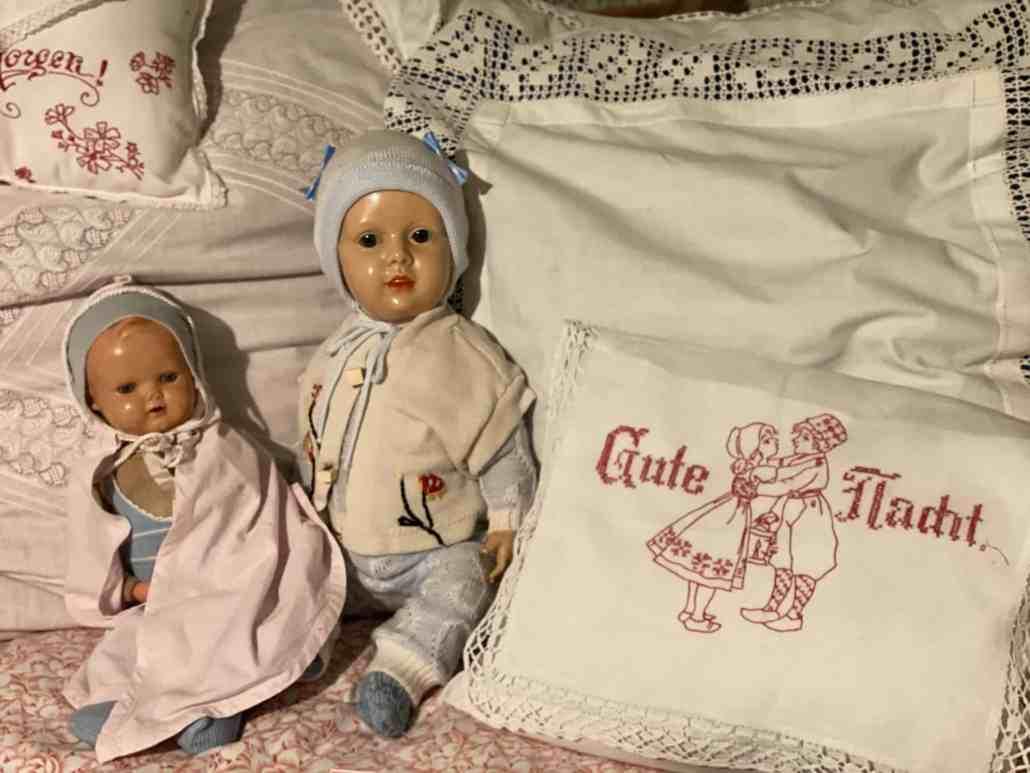 Zwei Puppen neben besticktem Kissen