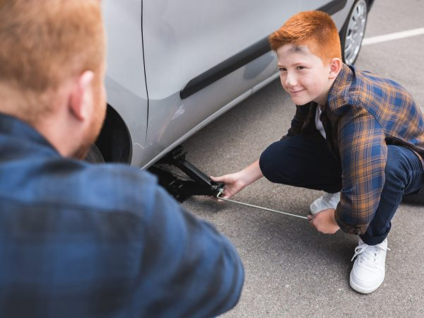 son lifting car with floor jack for changing tire and looking at father