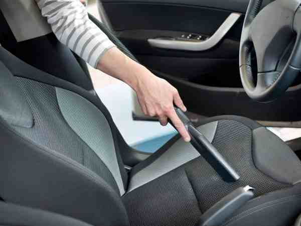 Autositz wird mit einem Staubsauger und einer Fugendüse gereinigt