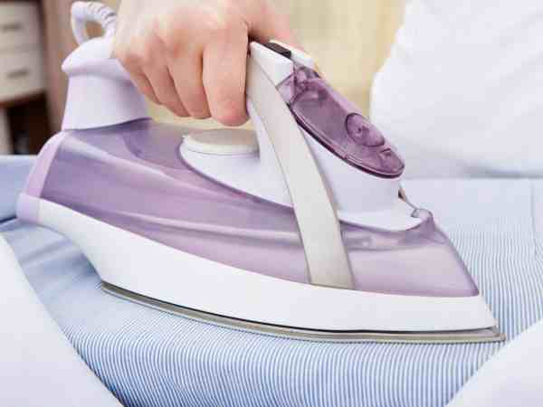 Close-up Of Woman's Hand Ironing Clothes On Ironing Board
