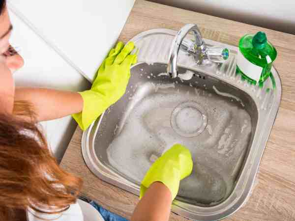 High Angle View Of Woman Cleaning The Sink In The Kitchen Using Liquid Detergent