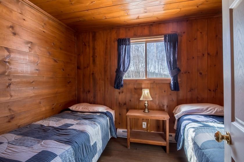 Chalet #8 de la Pourvoirie Mekoos. Chambre 2 avec un lit simple et un lit double