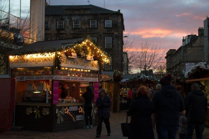 Glasgow, Scotland. Christmas market. Silhoette of people walking around the market stalls with sunset sky.