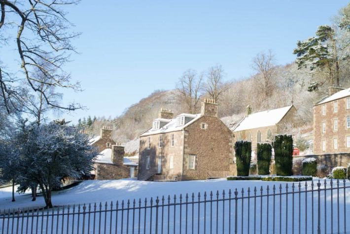 New Lanark Mill Hotel. Photo of buildings in the snow and the sun is shining