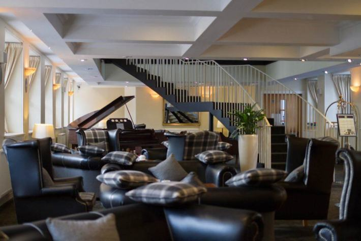 New Lanark Mill Hotel. Photo of the reception area with leather arm chairs, a piano and a staircase leading to the next floor
