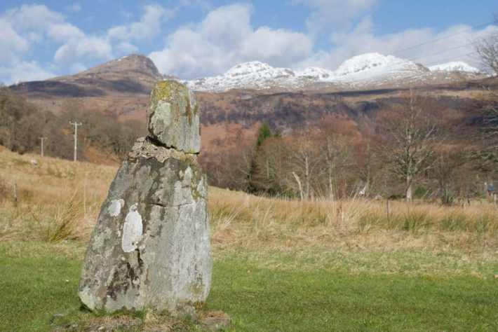 Photo of Fingal's Finger. A small standing stone in highland Perthshire. Snow capped mountains in the background