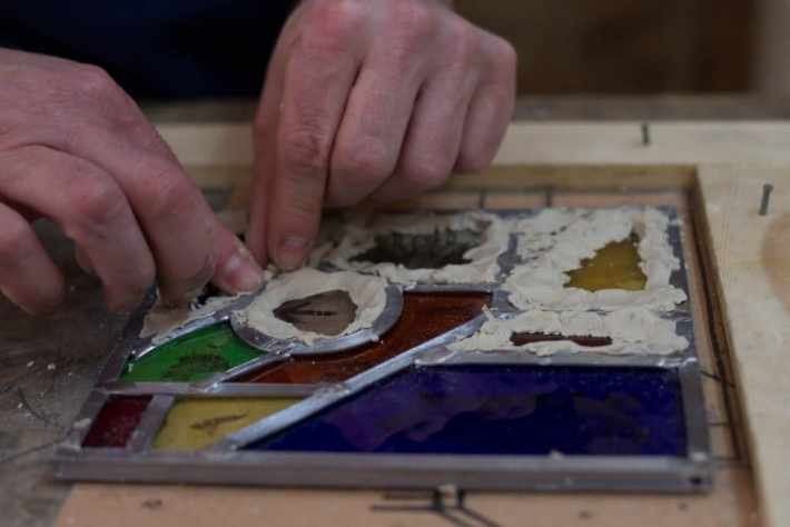 Photo of a person using putty around their small stained glass window during a workshop