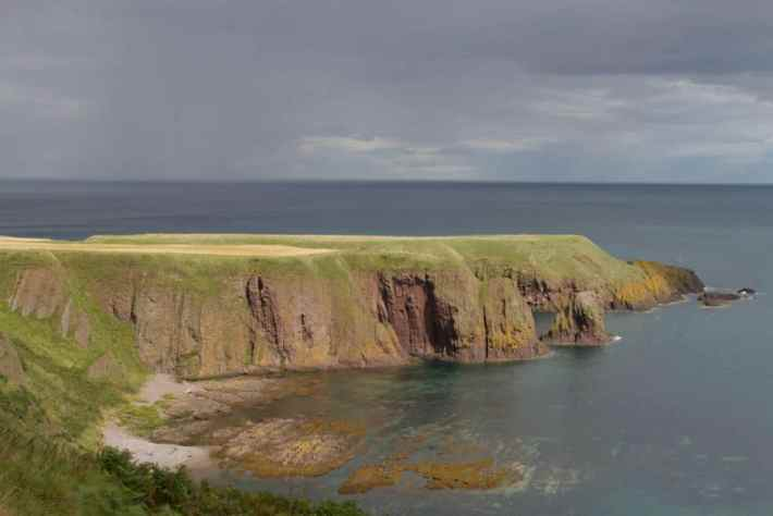 Dunnottar Castle, Aberdeenshire. Photo of the rugged coast. The sky is dark and moody but the headland is in sunlight