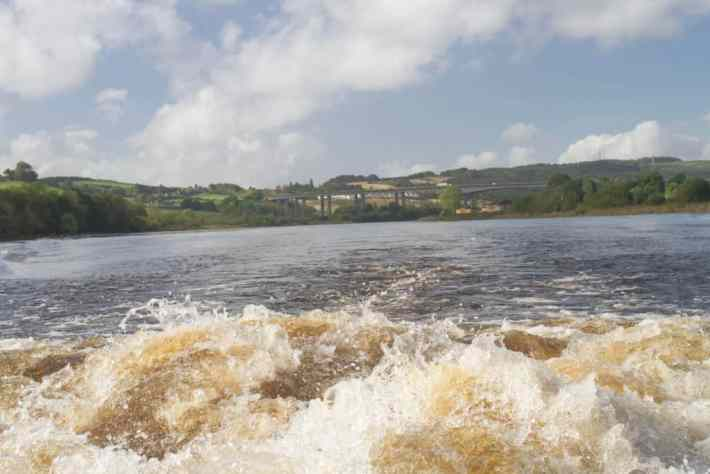 River Tay boat trips, Perth, Scotland. Photo of white water at the back of a boat. In the background is a bridge, trees and blue sky