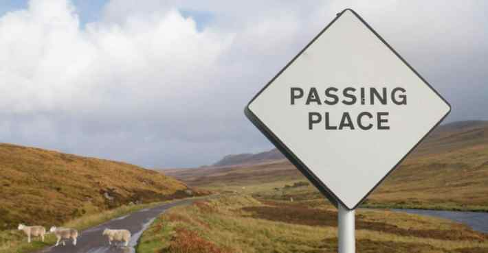 "A ""Passing Place"" road sign in the foreground with sheep crossing the road behind it."