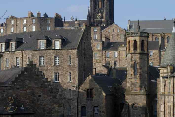 Layers of buildings and rooftops. Tall townhouses, church towers in Edinburgh.