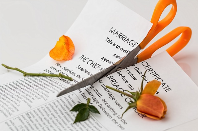 Orange scissors cutting through marriage certificate