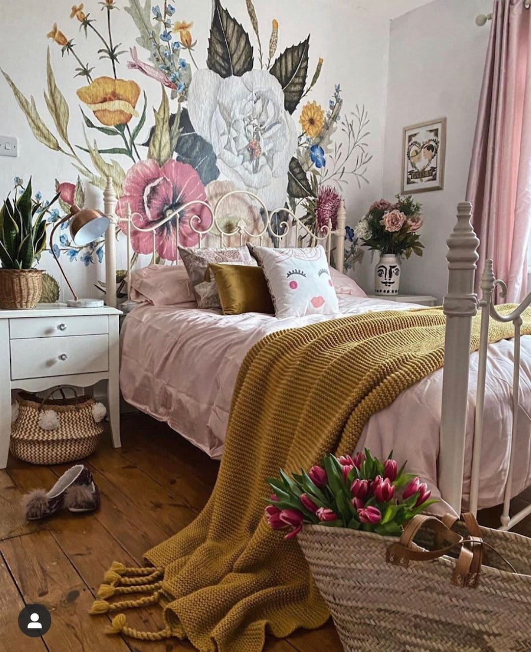 floral wallpaper in the bedroom with pink bedding, mustard throw and tulips in a basket.