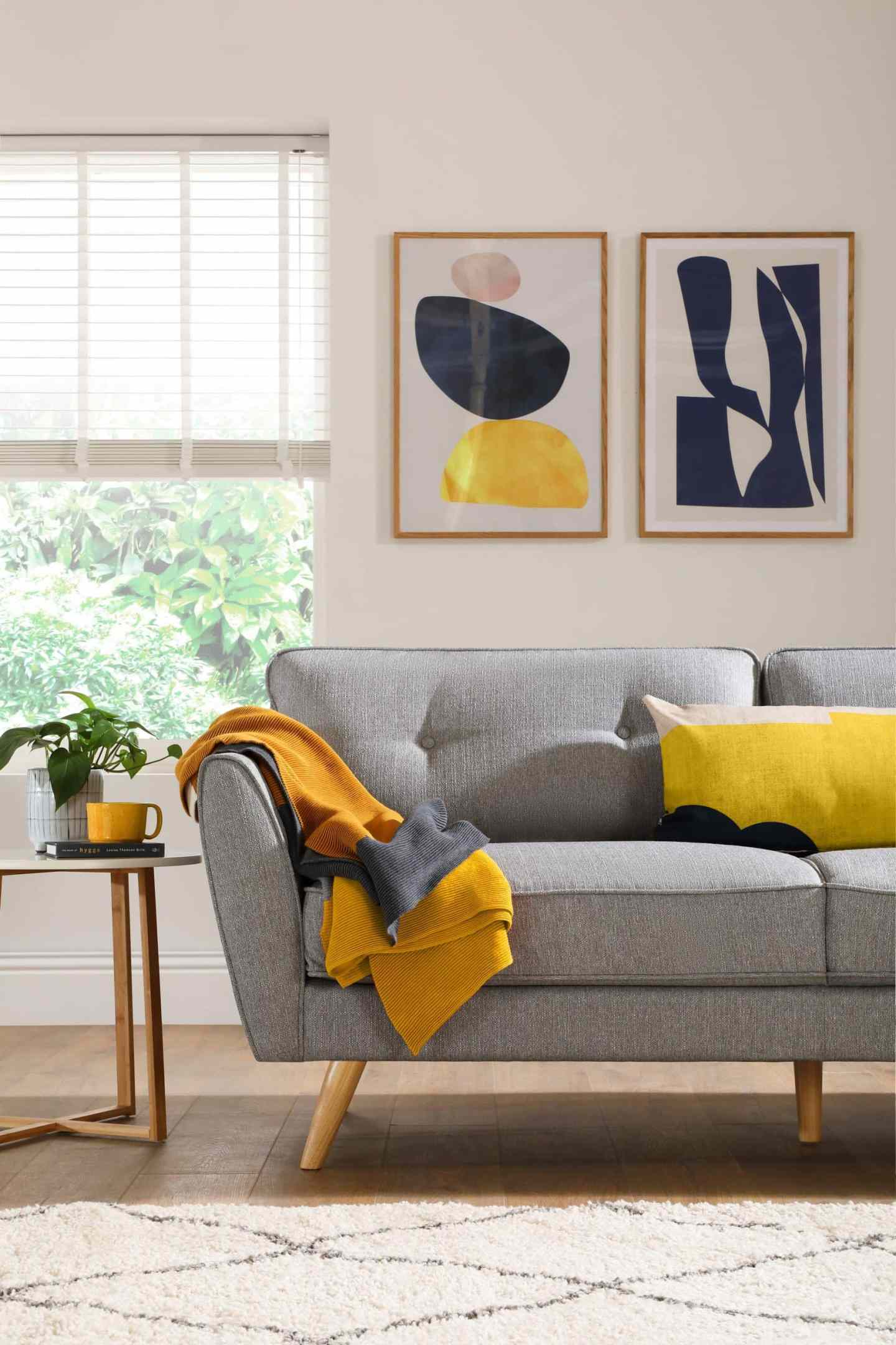 grey sofa with bright yellow throw and cushion and abstract art