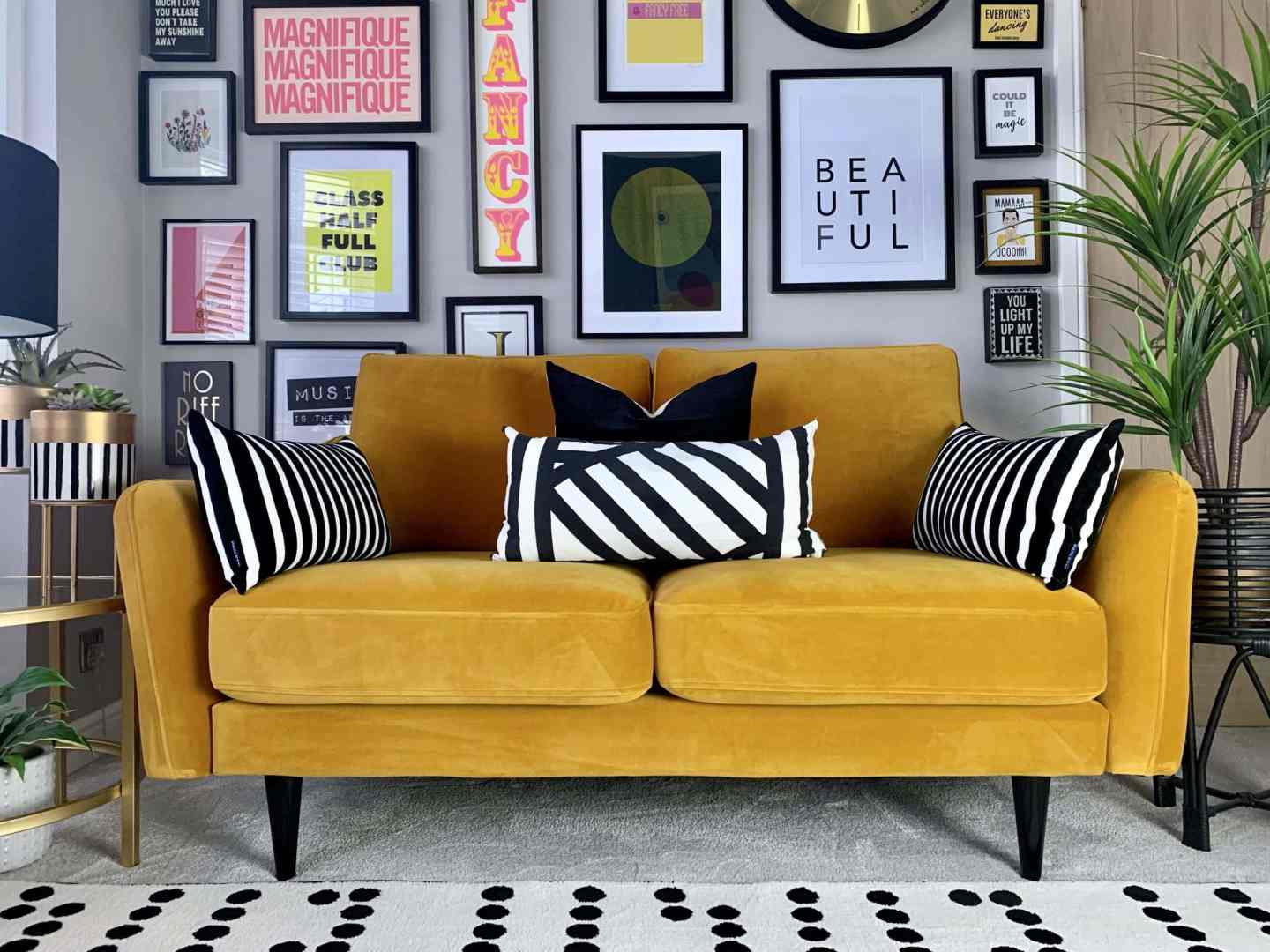 bright yellow velvet 2 seater sofa with brightly coloured gallery wall and monochrome rug